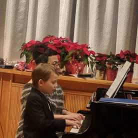 young boy playing a piano with his teacher