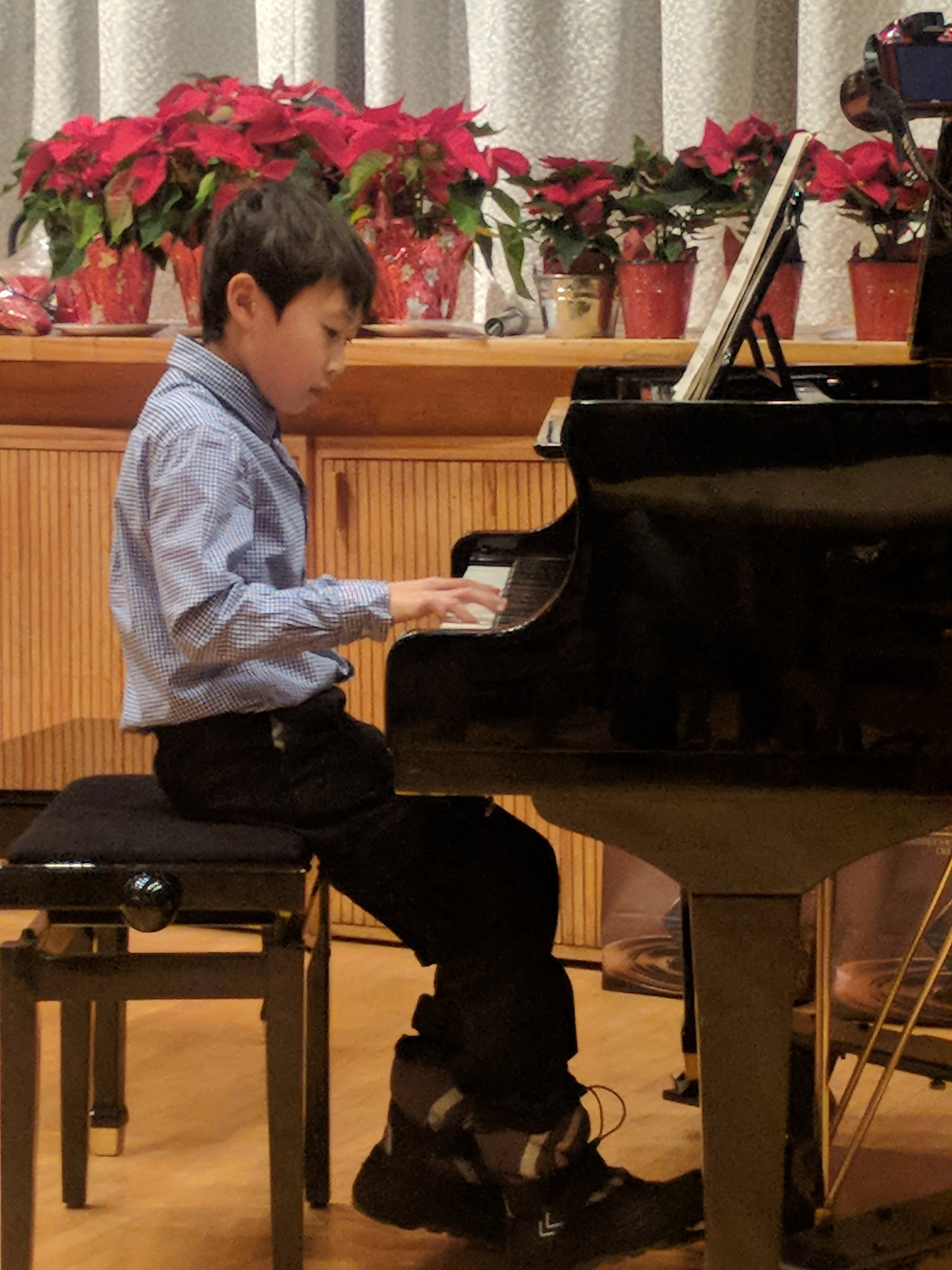 young boy learning to play a piano