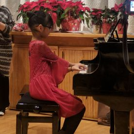 young girl playing a piano