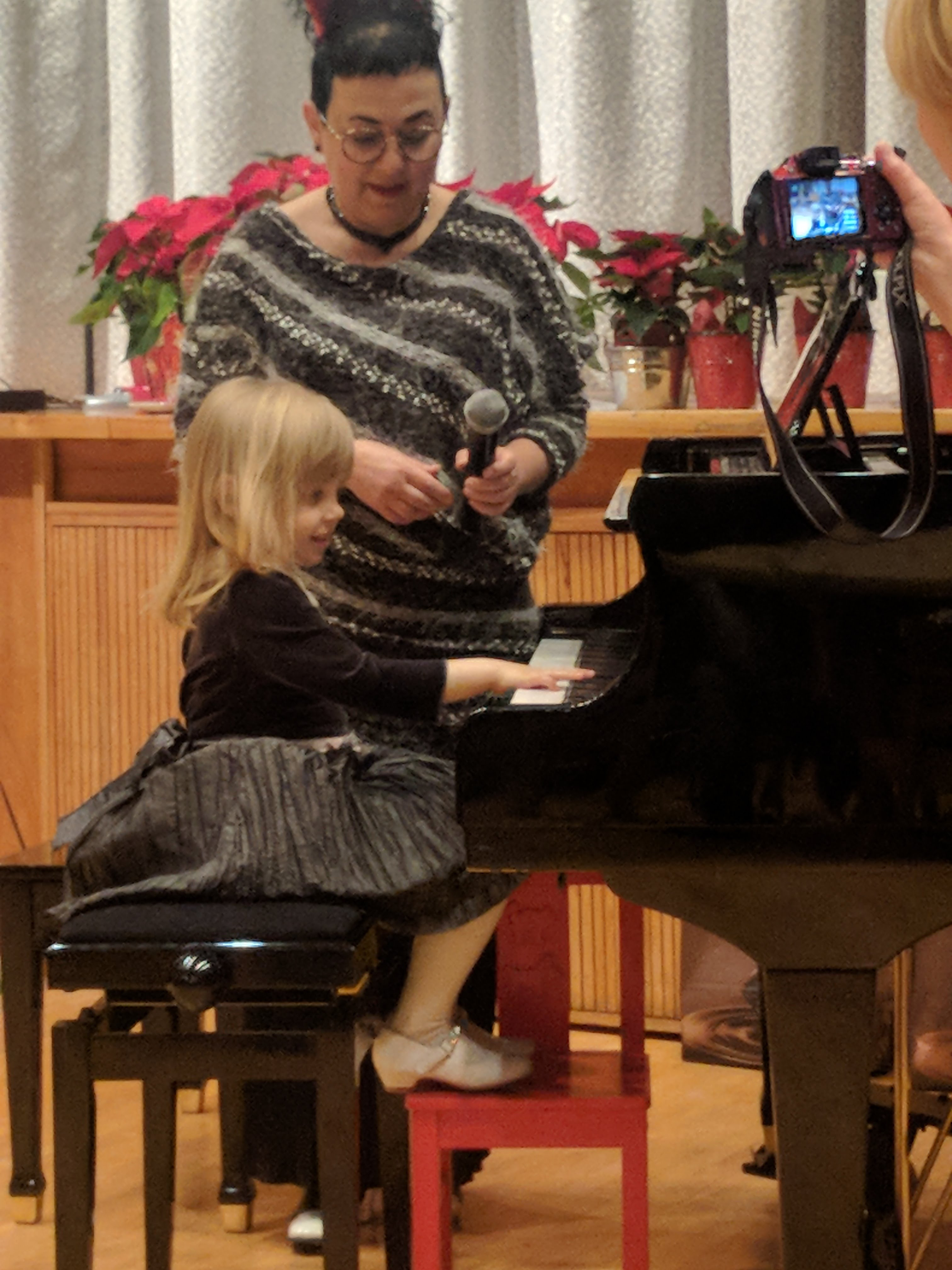 young girl playing a piano in front of an instructor