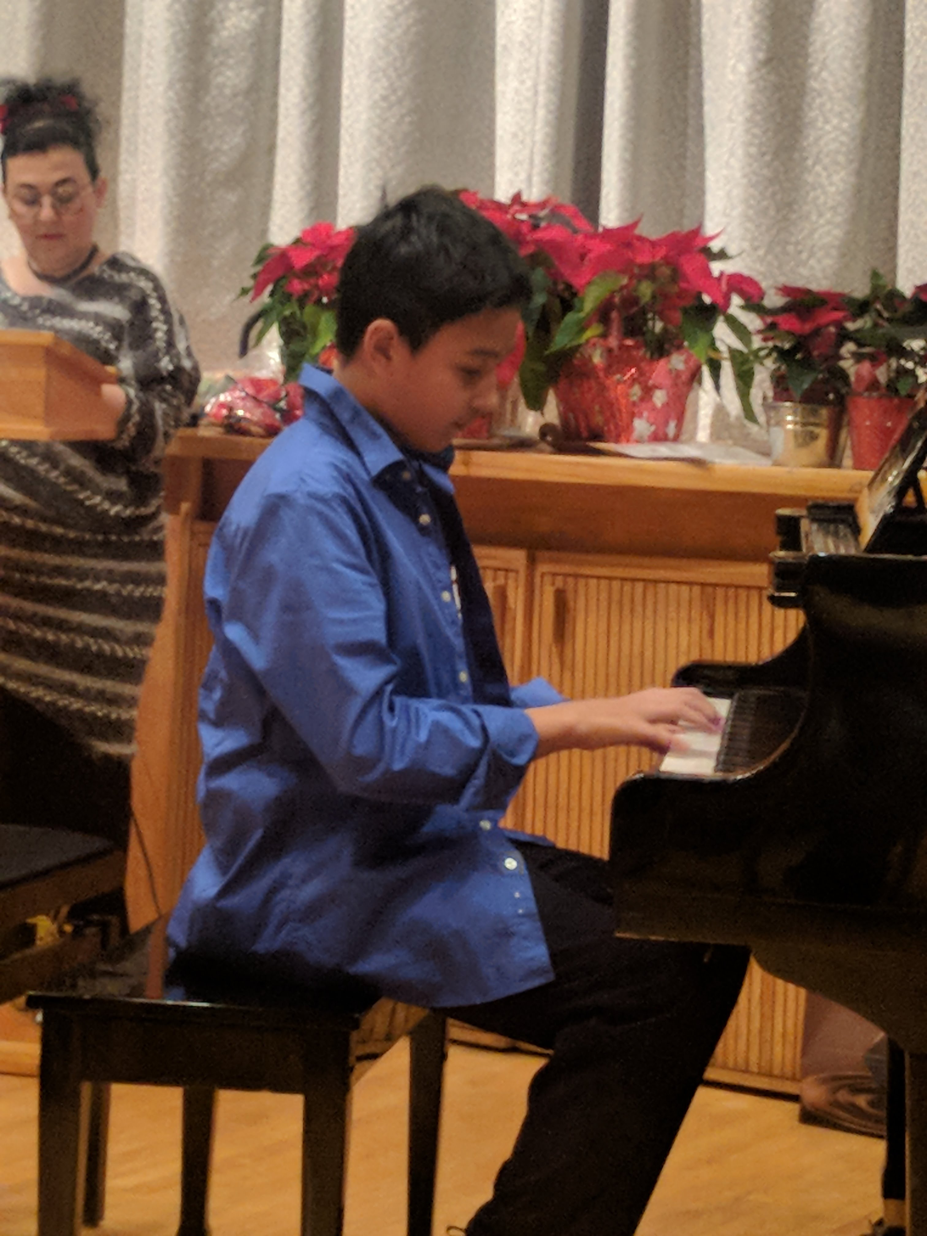 young boy in blue jacket playing a piano