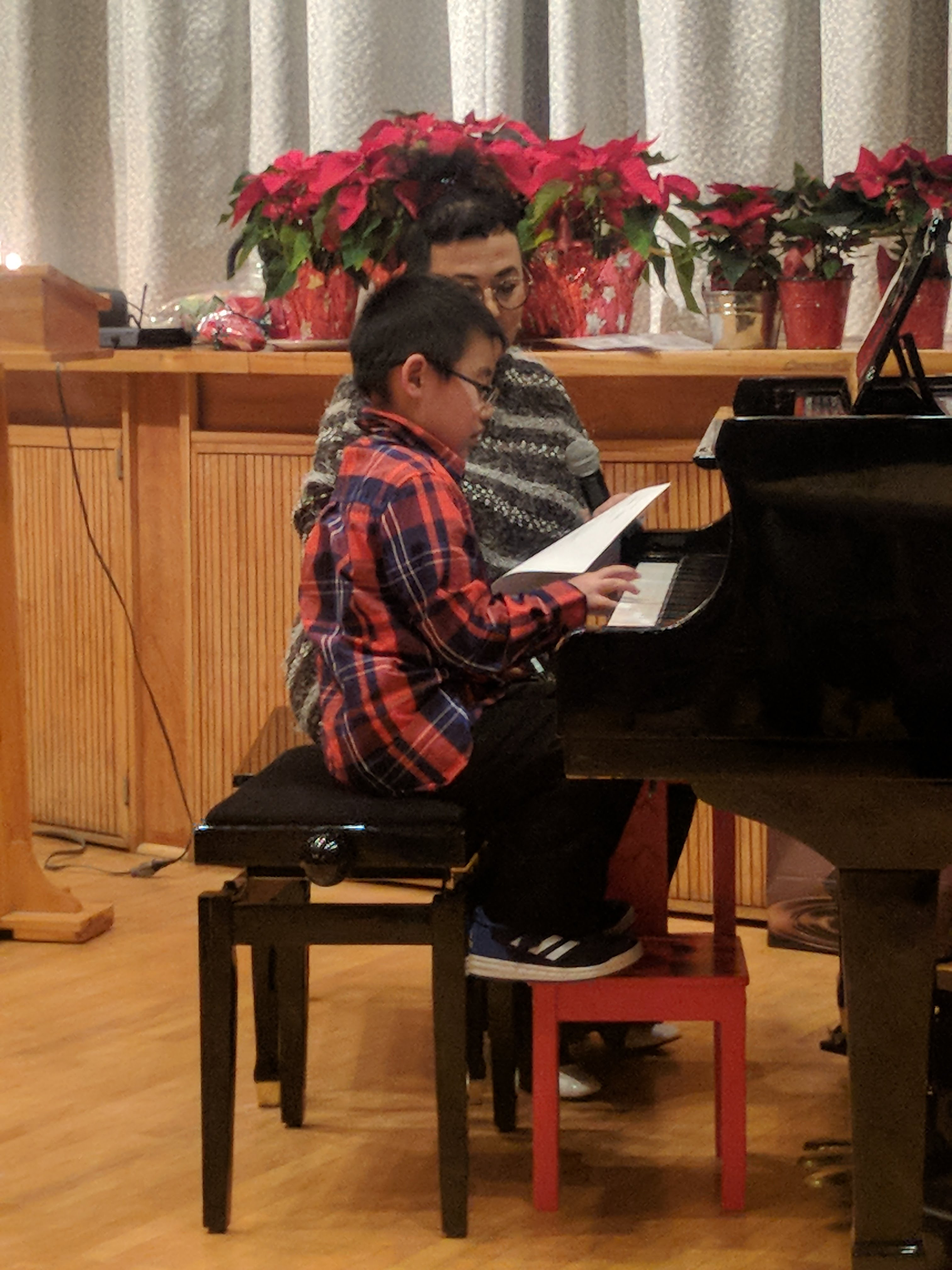 young boy playing a piano in front of a teacher